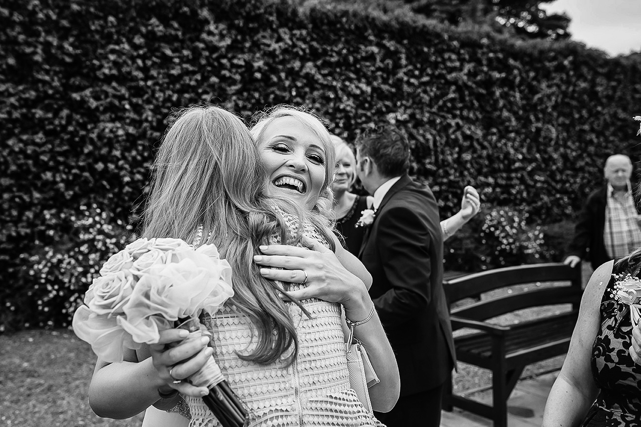 bride and bridesmaid hugging