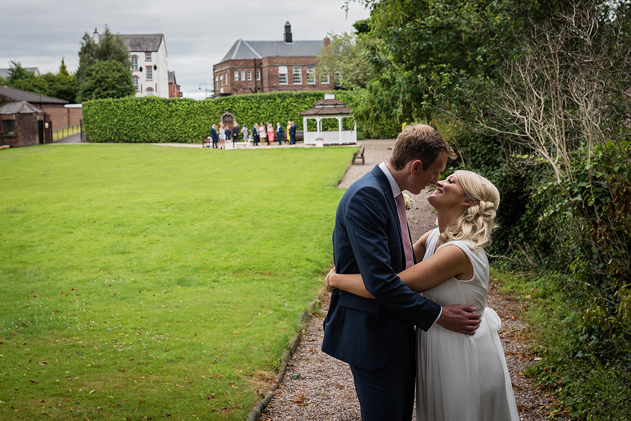 bride and groom kissing in the grounds of knowsley registry office