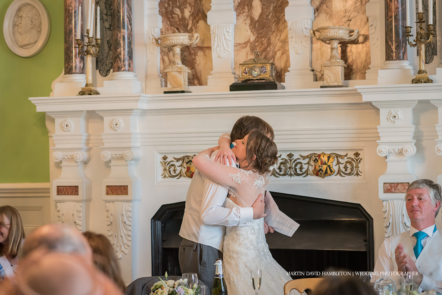 bride hugs groom during his speech