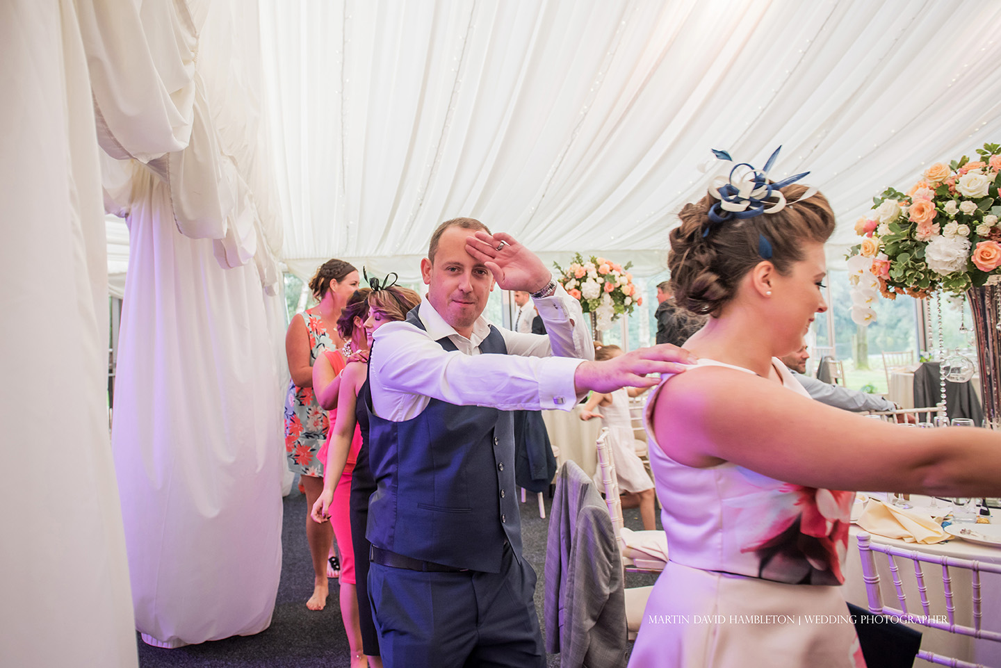 wedding guests dancing in a conga line